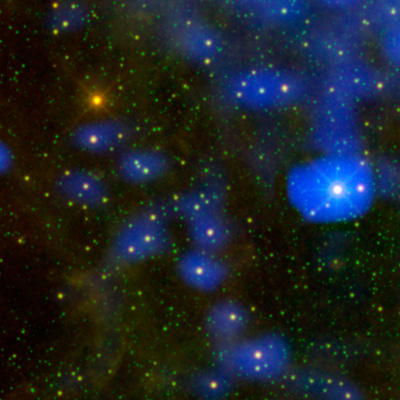 A star field containing myriad green stars and a dozen or more stars surrounded by blue fields.
