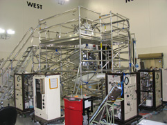 WISE spacecraft is surrounded by scaffolding and instruments. It is barely visible through the scaffolding.