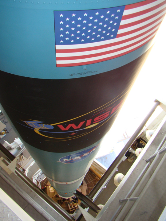 Looking down the Delta rocket, at the American flag and a WISE logo on the rocket.