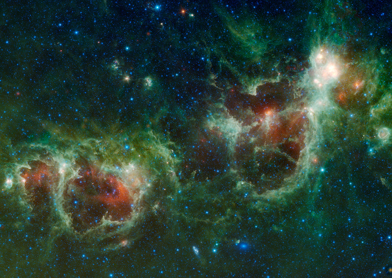 Two distinct multicolored clouds are visible.  The one on the right, which resembles a human heart, is called the Heart Nebula and the one on the left is called the Soul Nebula.