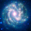 A glowing blue/white pinwheel-shaped spiral galaxy in field of stars.