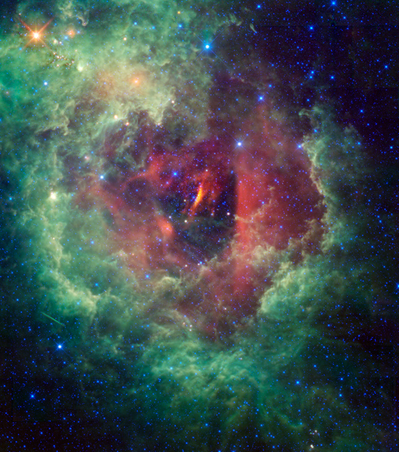 The multicolored cloud which spans the image is actually the Rosette Nebula located within the constellation Monoceros.