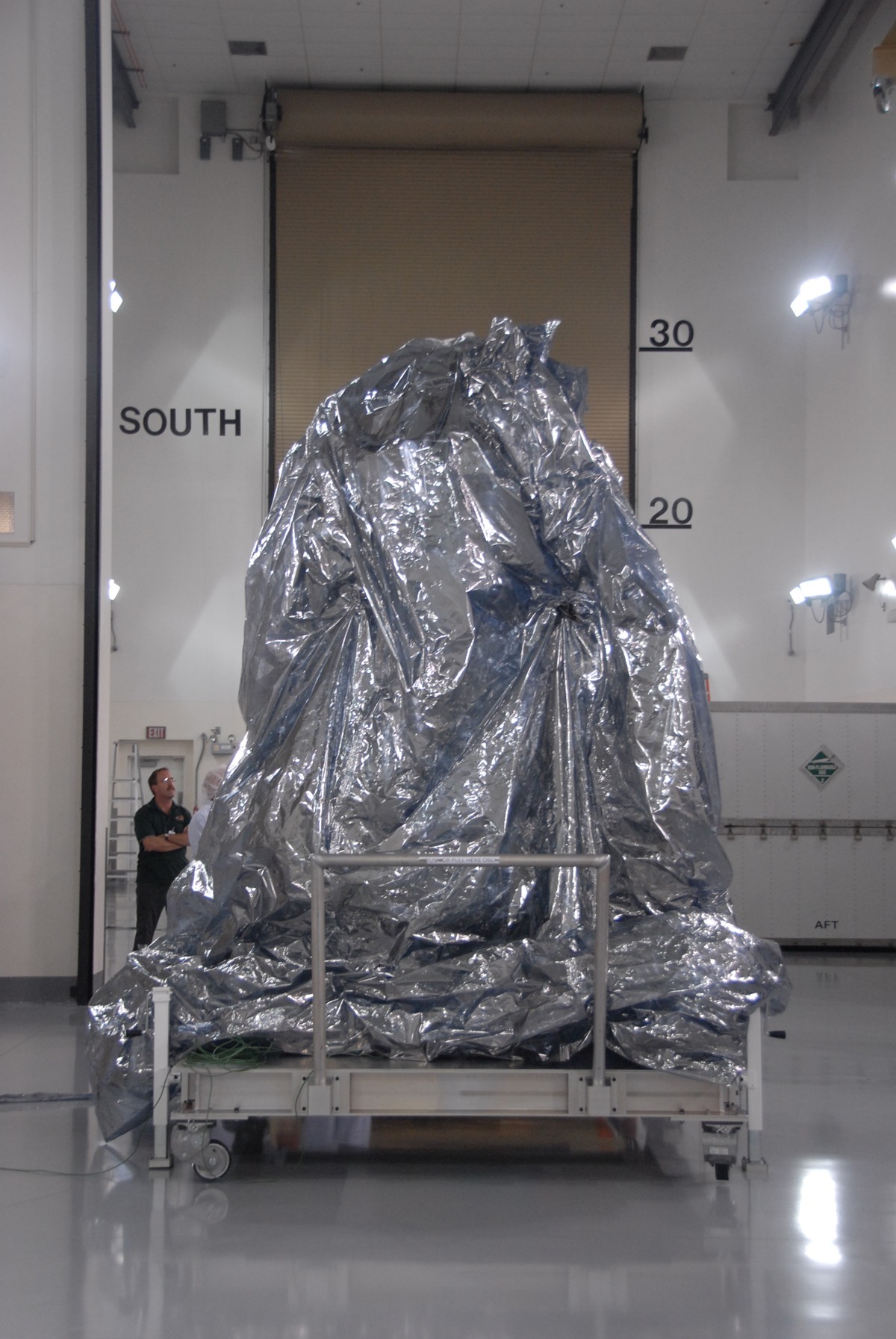 WISE spacecraft sits with a protective covering.