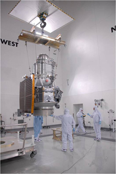Workers working on WISE with the full flight system all assembled.  The payload, solar panel, and antennae are all attached.