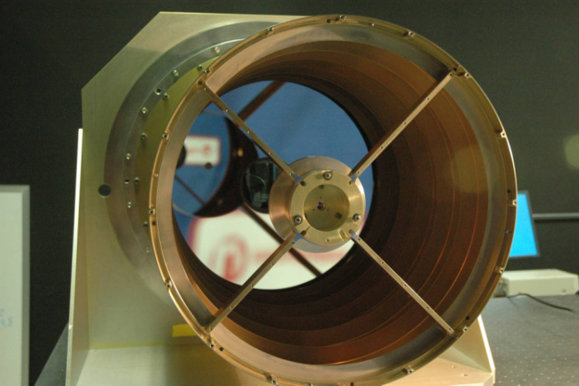 View down the barrel of the telescope.  Vaguely resembles a still fan, with a small center piece, and four thin blades connecting the center piece to the exterior of the telescope.