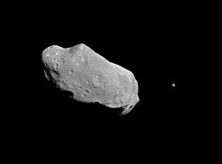 Image shows a grey rock, which is the asteroid, in a black environment, which is space.